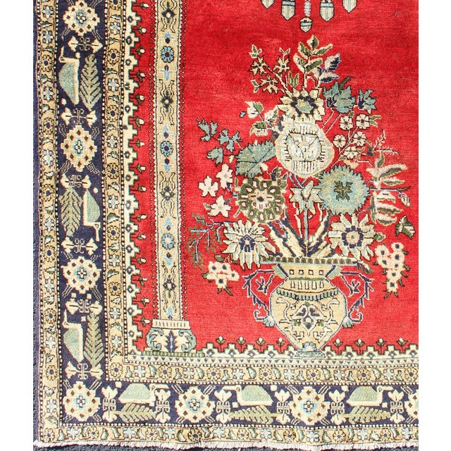 This beautiful Semi Antique Qum rug bears a prayer rug design and a flower bouquet resting under an ornate chandelier n...