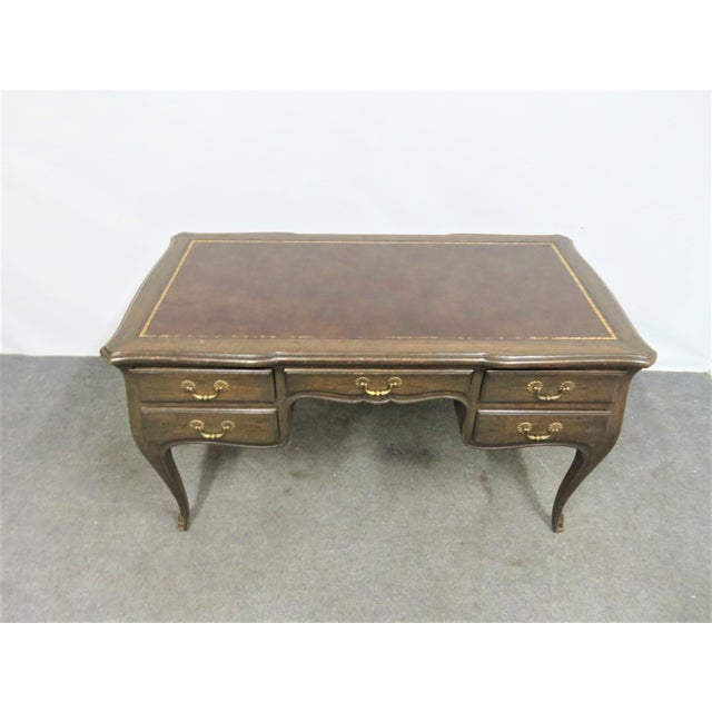 Quality made Louis XV style writing desk with faux walnut finish. Features brown leather top with gold trim, 5 drawers, 2...