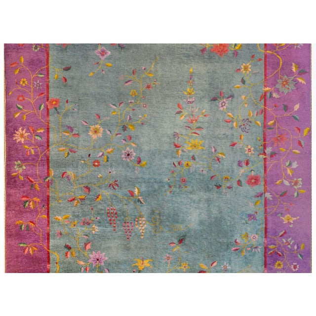 A brilliant early 20th century Chinese Art Deco rug with a pale mint green field surrounded by a wide fuchsia border with...