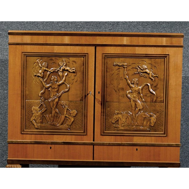 Intricately hand-carved storage cabinet or dry bar of various woods including walnut, mahogany and dark flame birch....