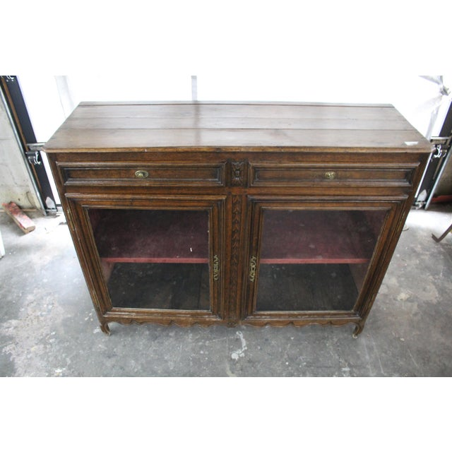 19th century antique glass door sideboard made of solid oak. This piece features dual cabinets complete with shelves and...