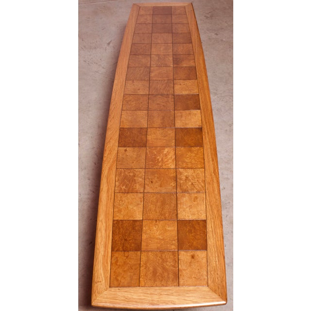 This extraordinarily long oak coffee table with inlaid burlwood checkered squares features slim tapered inset legs with...