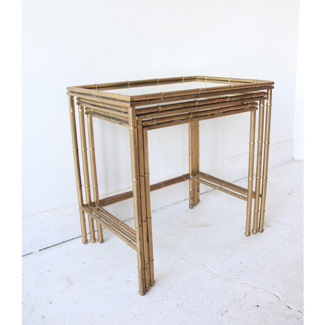 This is a vintage nesting table set, made in Italy. Gorgeous brass faux bamboo design with glass tops. Fit together...