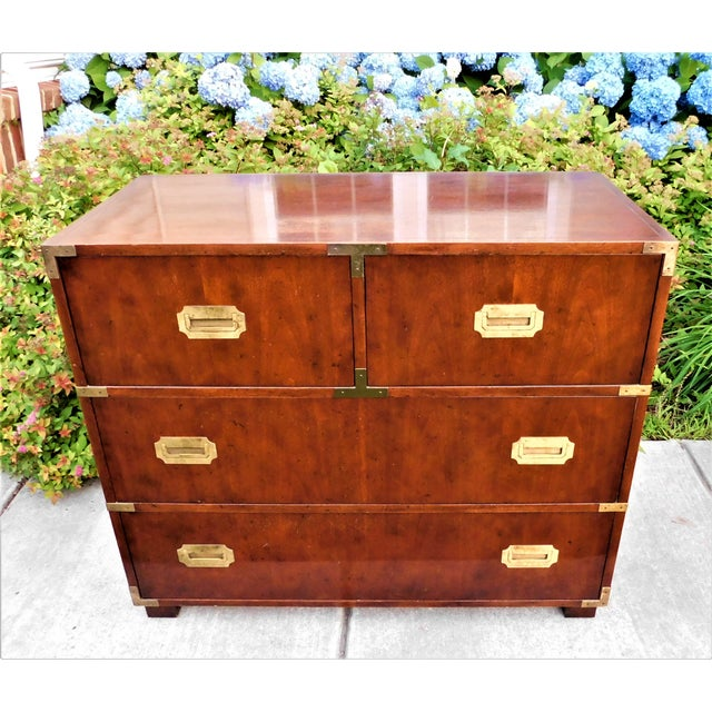 An extraordinary Campaign style chest of drawers by Baker Furniture. The chest features gorgeous wood grain and brass...