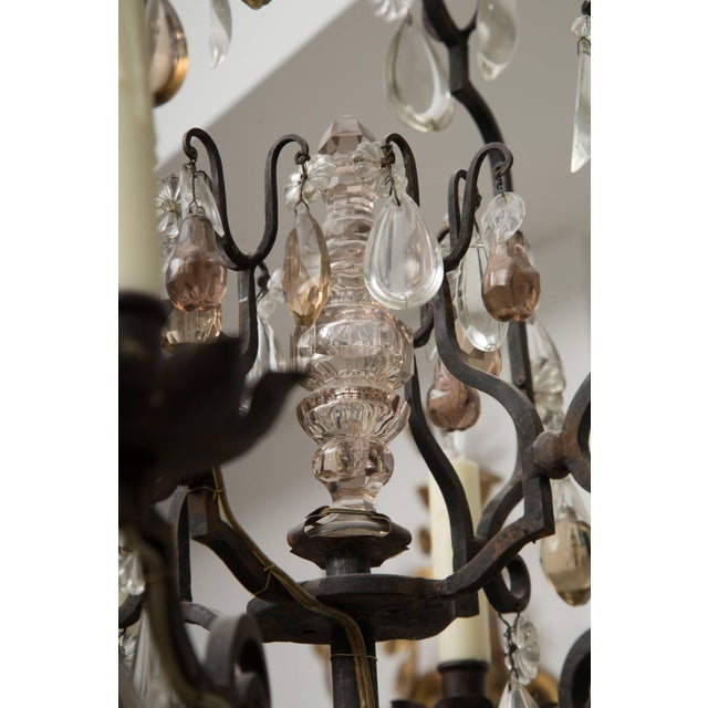 This is a romantic lantern-form French bronze eight-light chandelier, with a variety of glass pendants representing...