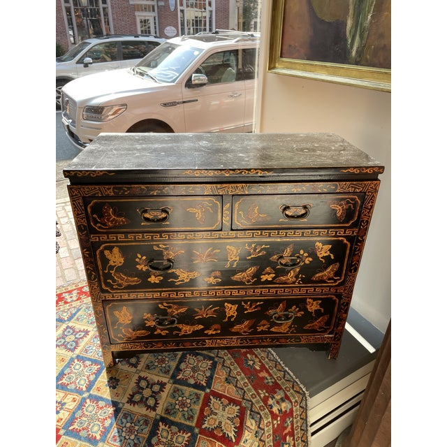 This is a lovely chest of drawers with beautiful detailing. It is black with gold and red butterflies and florals on it....