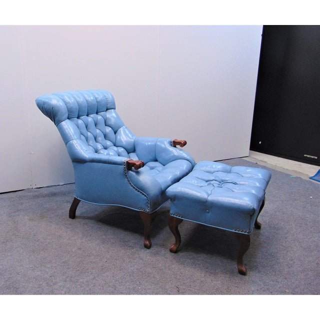 Chesterfield style lounge chair and ottoman, light blue tufted leather, cherry wood legs and arms. Ottoman measures 24...