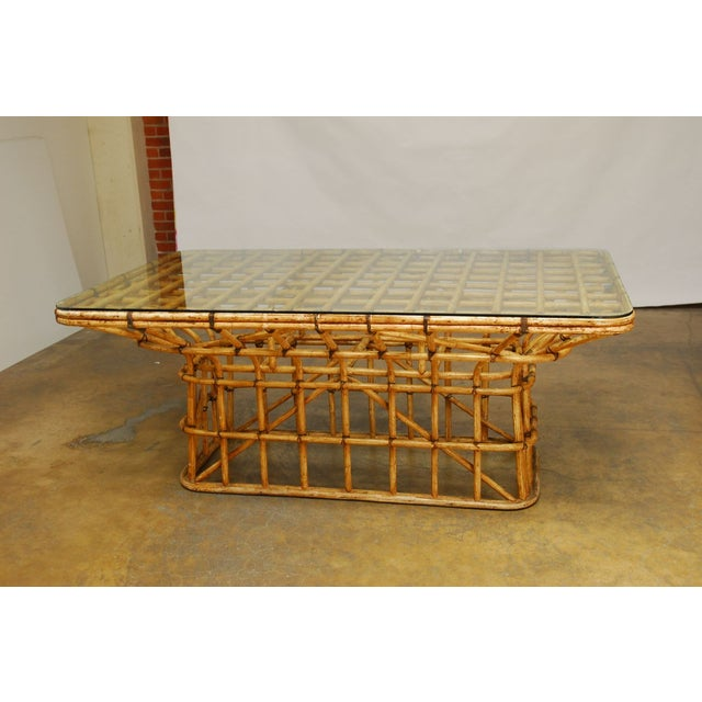 Extraordinary dining table constructed of bent bamboo with leather strapping. The rare table features an open lattice...