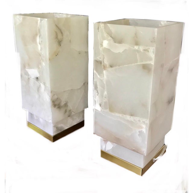 A gorgeous pair of pure alabaster table lamps mounted on brushed gold finish, metal bases. The alabaster forms a hollow...