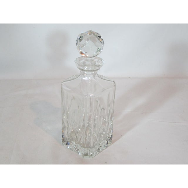 Square shaped decanter with faceted designs on four sides. It is topped off with a large faceted stopper.
