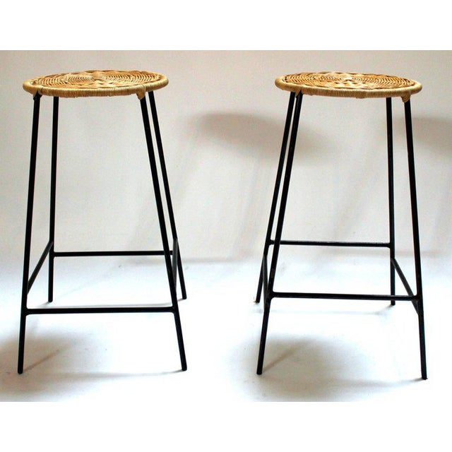 Pair of 1960s metal bar stools with woven wicker seats in the style of Arthur Umanoff. Price is for the pair.