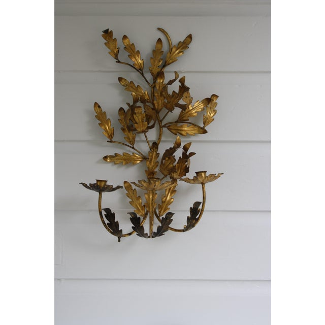 This vintage Italian gilt toleware wall candelabra holds 3 candles or you could have it converted to electric if desired....
