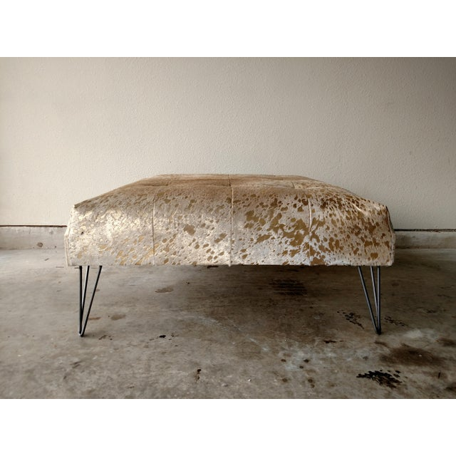 Metallic gold and light beige cowhide ottoman with metal hairpin legs. This ottoman was made in the USA