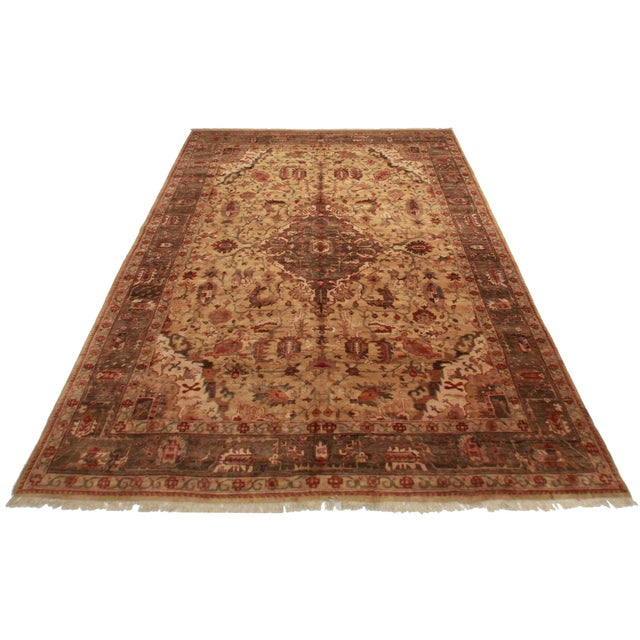 Featuring an antiqued look, this oversized, hand-knotted Persian-style rug is crafted of wool. Colors include a khaki...