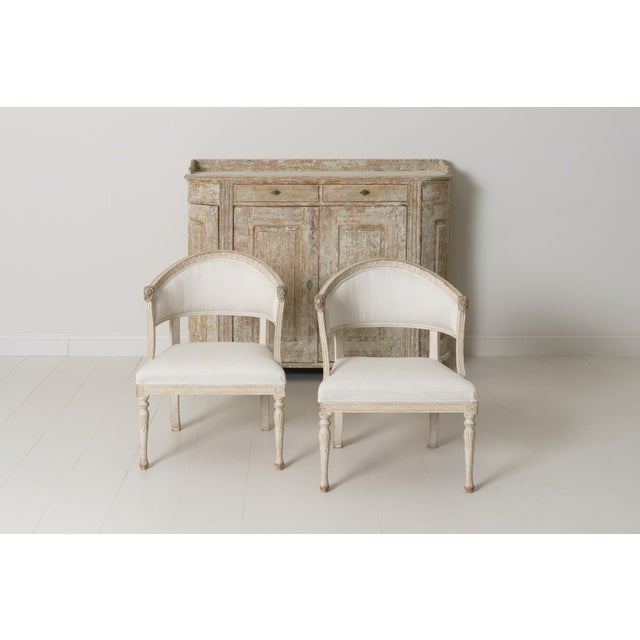 A Swedish Gustavian style pair of antique klismos armchairs. These stunning chairs have barrel backs with cravings of...