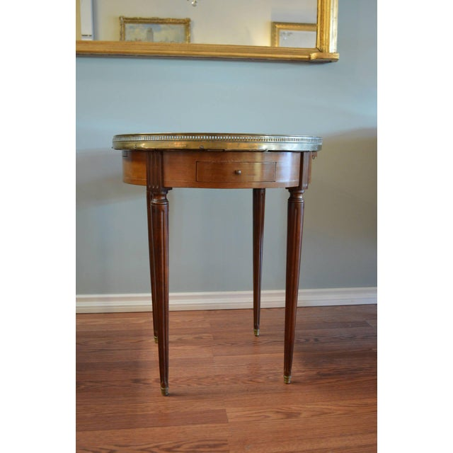 Louis XVI style mahogany bouillotte table with a very nice original marble top. There is a bronze gallery and there are...