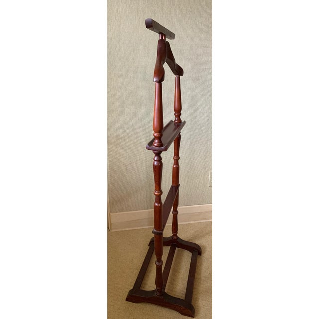 A handsome mahogany clothes stand fitted with a niched crosspiece for holding small items. The turned vertical supports...