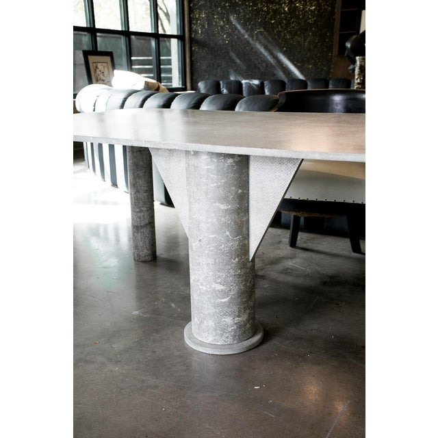 Generously scaled desk of concrete composite with geometric pedestal and cylindrical legs. Italy, 1980s.