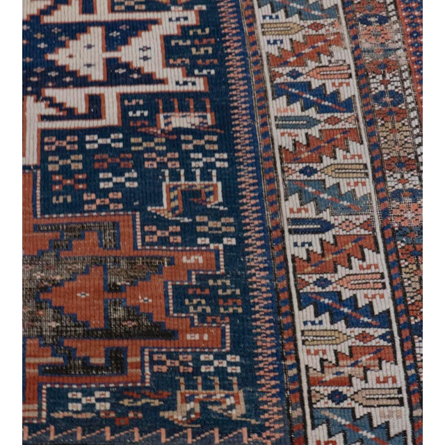 This antique Caucasian rug features a deep blue field scattered with polychrome S-motifs, stylized animals and polychrome...