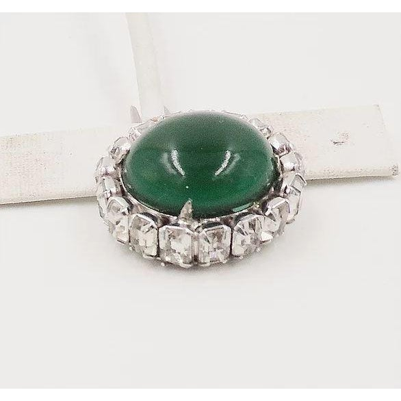 """1950s rhodium plated open backed faux-emerald rhinestone cabochon hair clip. Marked """"Kramer of New York. Measures: 1 7/8..."""