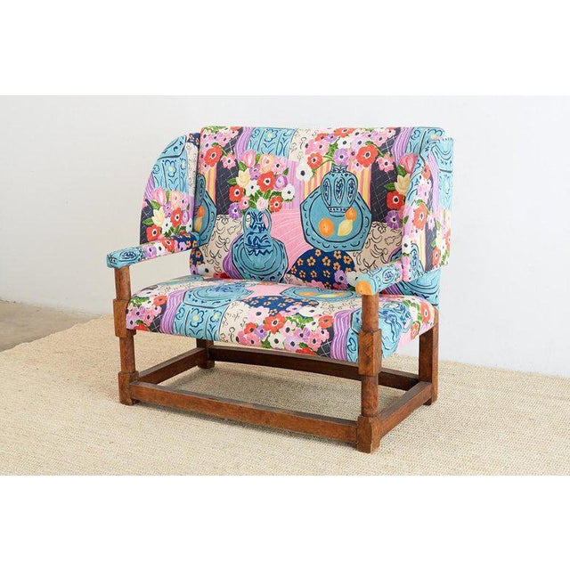 Fabulous antique English wingback settee featuring a colorful floral upholstery after Matisse. Constructed with thick...