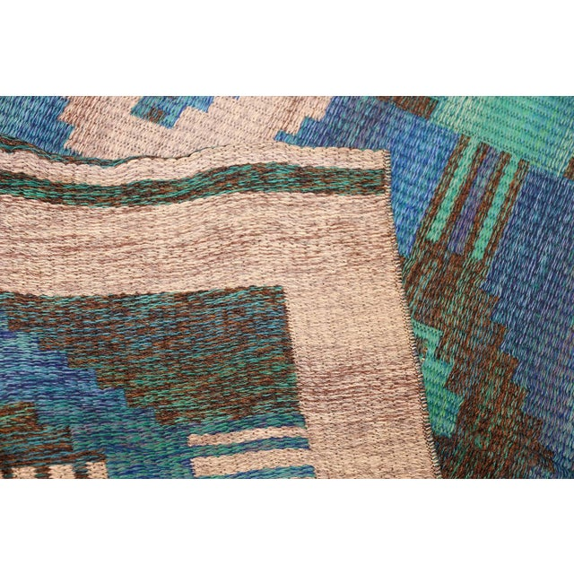 This cleverly composed vintage Swedish Kilim features a graphic repeating pattern that is rendered in an alluring...