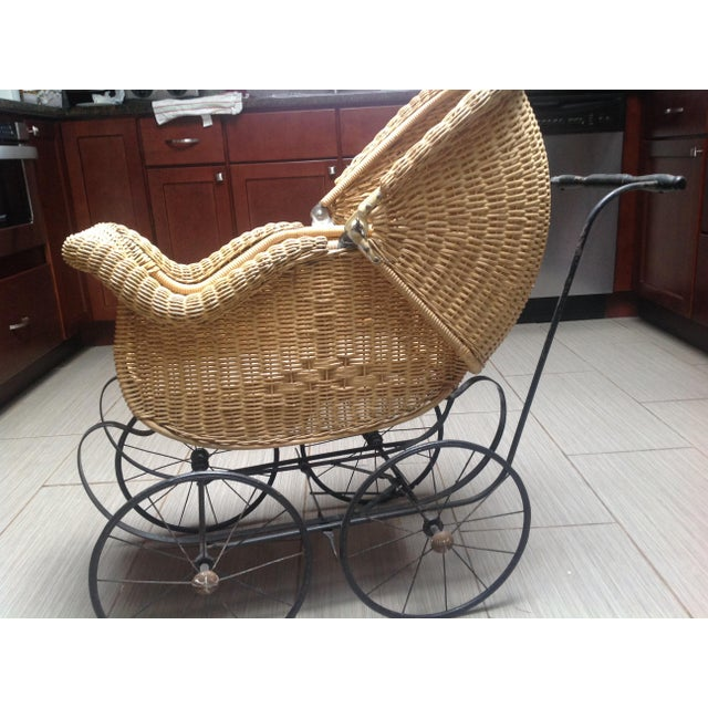 Victorian Vintage wicker baby buggy. Natural color wicker with wood handle and nice metal ornate frame. The hood has a...