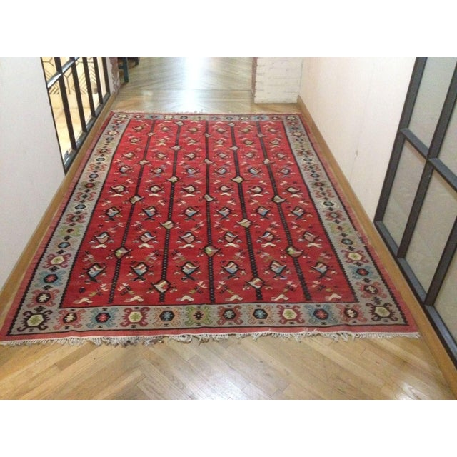 A darling red area rug with hand sewn bird and fish designs. 10' long and a little over 6' wide.