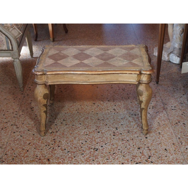 Small but beautiful side table from Italy. Early 19th century. The edges are gilded. Curved legs. The table is hand...
