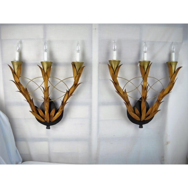 Pair of elegant electric wall sconces featuring a classical laurel-leaf three-arm design with black base and white faux-...
