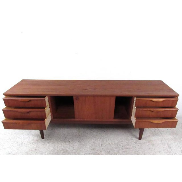 This uniquely sized vintage sideboard features a combination of six storage drawers and sliding cabinet doors. Quality...