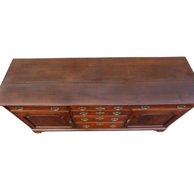 Rectangular top over four central graduated drawers flanked by a drawers and a door. Great color to the wood. Original...