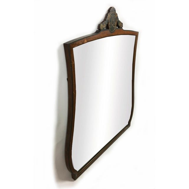 A large mirror in a unique shape. Frame is vintage wood with an English Crest on the top frame. Make a statement with this...