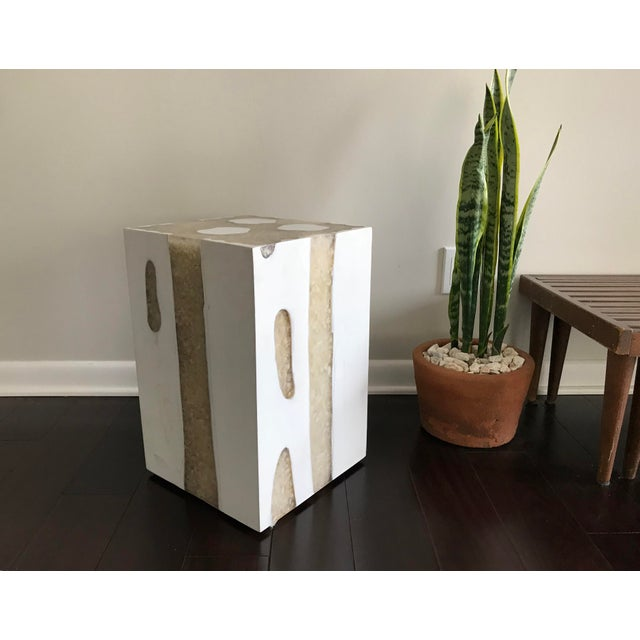The square Mieke Side Table in Off White from Made Goods features a combination of white river stones and organic teak...