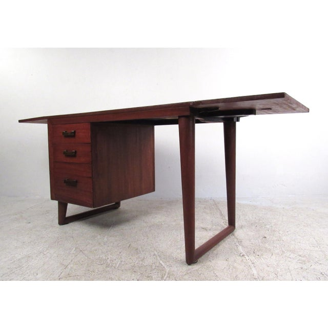 This unusual drop-leaf writing desk features sculptural sled legs, wide brass finish handles, and a Dual drop leaf design...