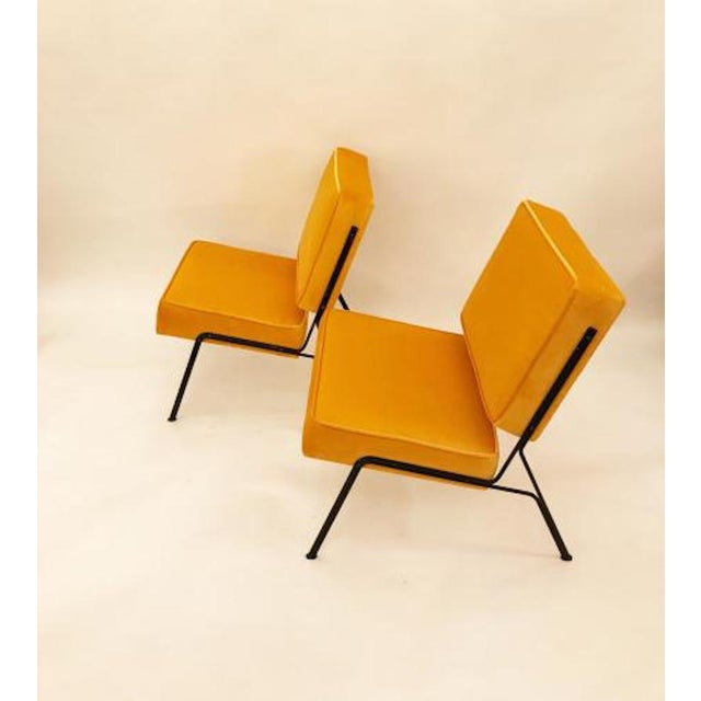 Two pairs of mid century slipper chairs each featuring frames in a matt black lacquered steel with splayed legs. The...