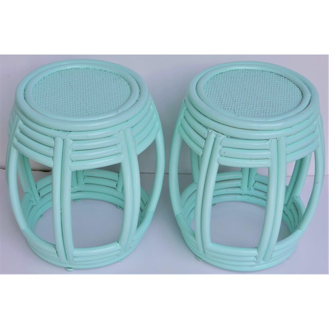 This is a pair of handwoven rattan barrel shaped side tables painted in a light aqua blue. These have caned tops and can...