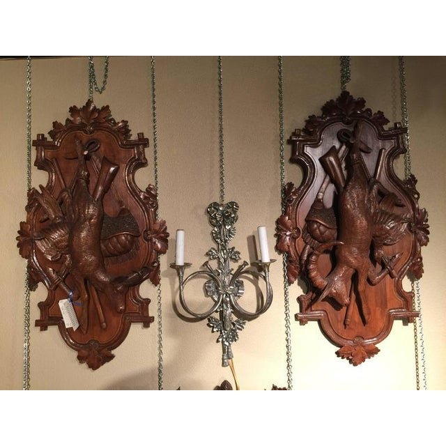 Exquisite pair of antique Black Forest hunting wall plaques from Switzerland, circa 1880; each featuring a large deer or...