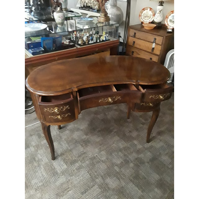 Beautiful kidney shaped desk. I believe it's from the 60's -70's. The drawer pulls are unique and fit the desk perfectly....