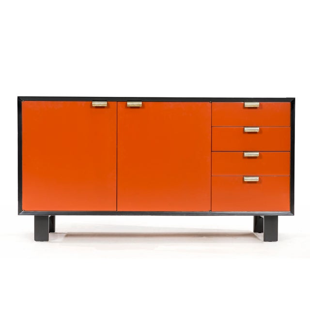 """Black lacquered credenza with """"coral"""" front face. Adjustable shelf and four pull out drawers. labeled as seen in picture."""