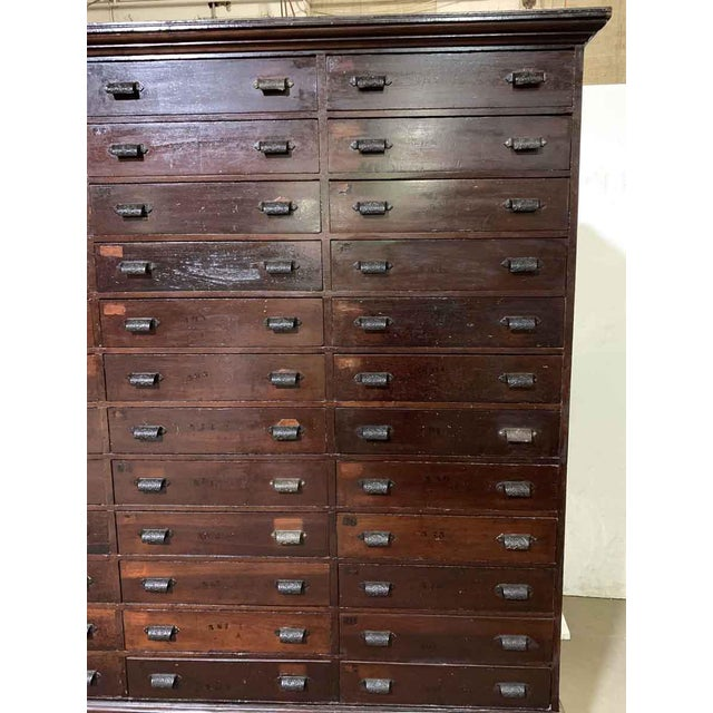 Old dark wood tone industrial cabinet housing 36 drawers with the original hardware. This piece has been recently...