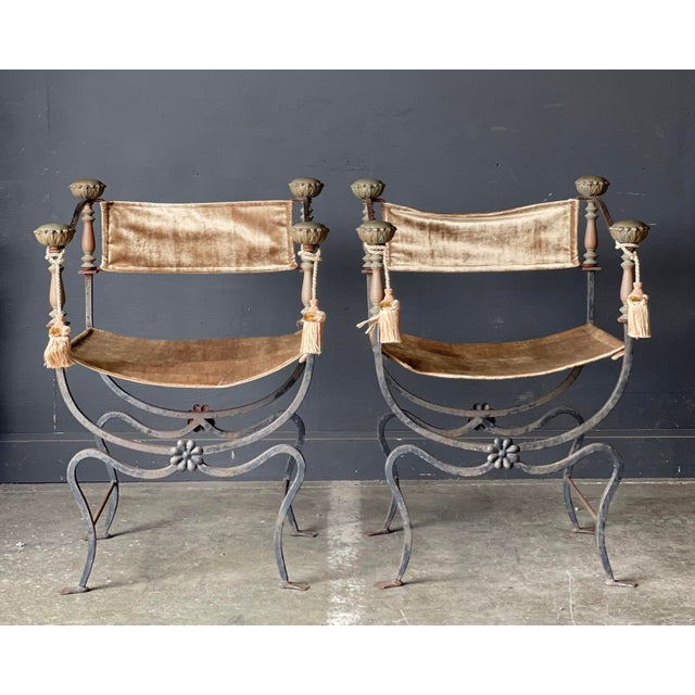 AN OUTSTANDING pair of early Italian Curule chairs. Heavy iron base with Solid Brass arms featuring Soft neutral velvet...