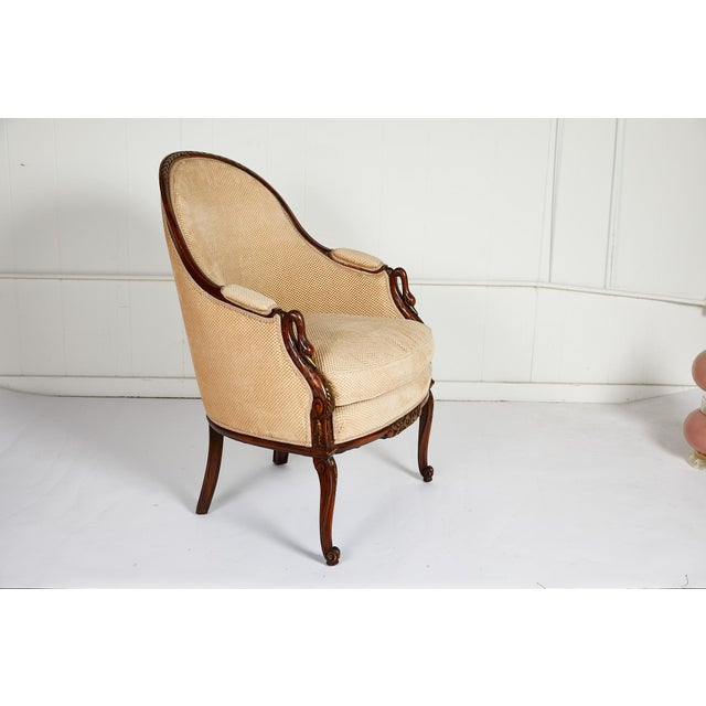 20th century upholstered tub chair of carved and gilded walnut made in the French Empire style. The floral carved and...