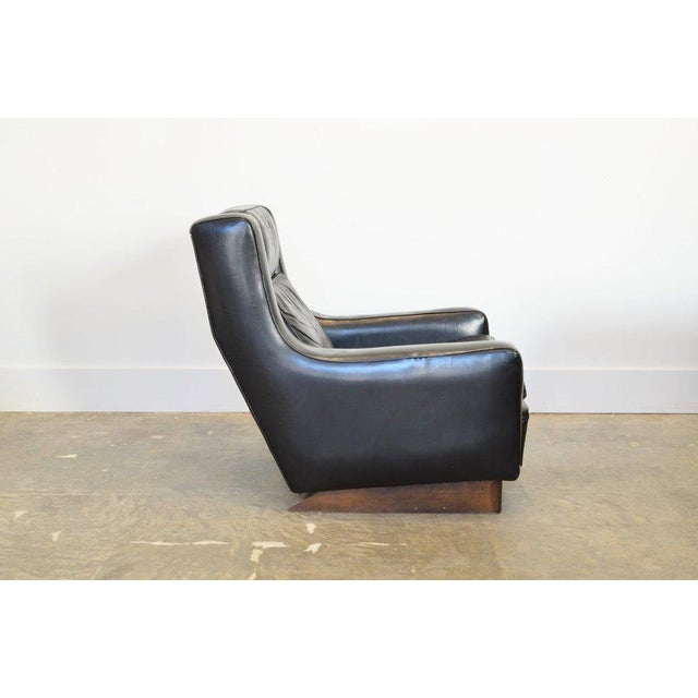 Vintage black leather comfortable XL lounge chair with wood runners.