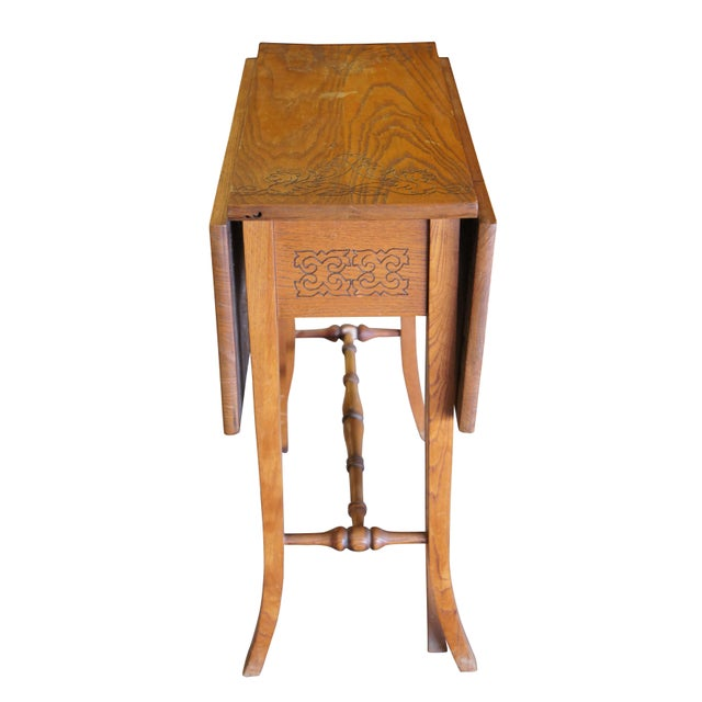 20th Century English oak gate-leg table. Exceptionally designed with a floral engraved top showing lion heads.
