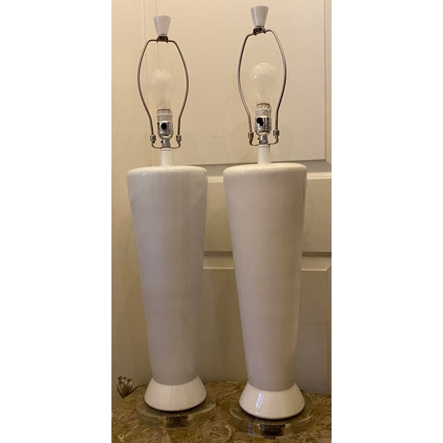 White Mid-Century Modern Ceramic Table Lamps - a Pair. Lamps are on lucite bases with matching finials.