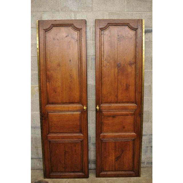 Pair of antique French Louis XVI style carved oak interior double doors with bronze rococo door knobs (A) Circa 19th...