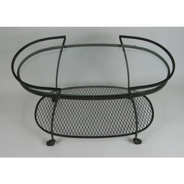 One of the best of Woodard's series of wrought iron rolling bar carts from the 1950s, this oval design from the Pinecrest...
