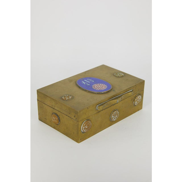 This is an antique brass box of Chinese make, with an inlaid cloisonné chrysanthemum and inscription. The inside of the...