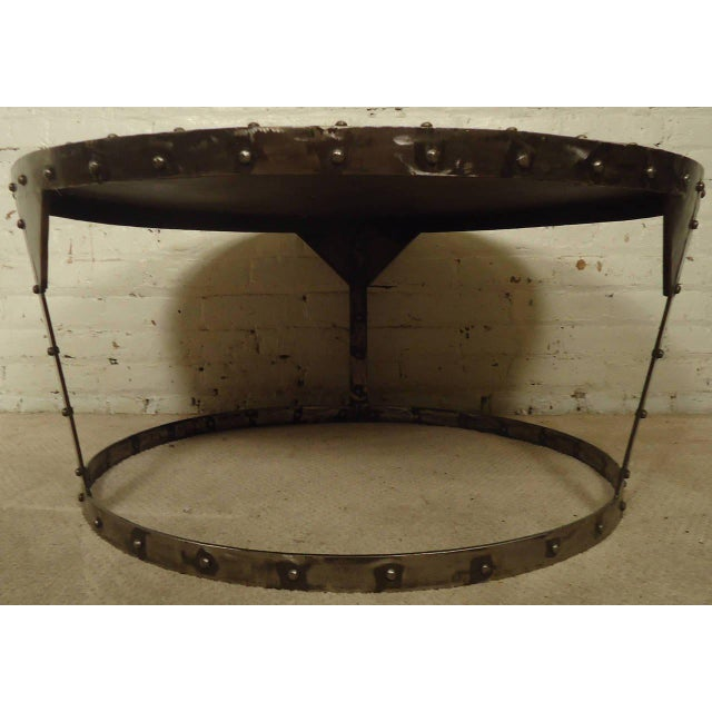 Distressed circular industrial-style metal coffee table, sturdy tapered base with riveted accents. (Please confirm item...